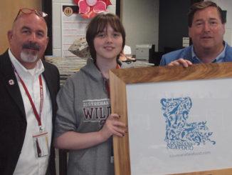 Destrehan High School Principal Stephen Weber, DHS senior Zoe Cloughessy and Louisiana Lt. Governor Billy Nungesser with Cloughessy's winning logo design.