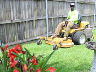 A worker with Quality Service Lawn and Landscape at work cutting grass.
